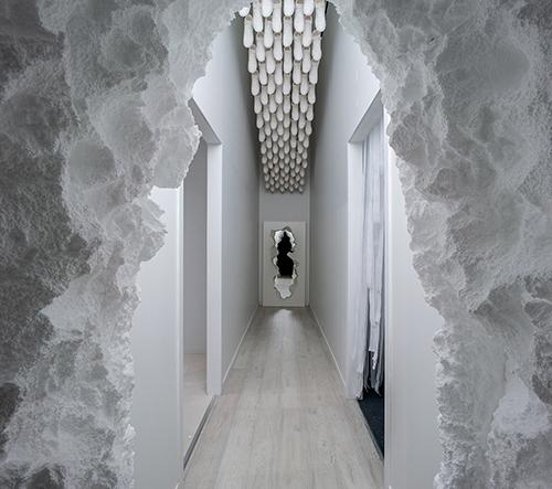 Fun House je bílá instalace s optickými iluzemi a bazénem plným kuliček
