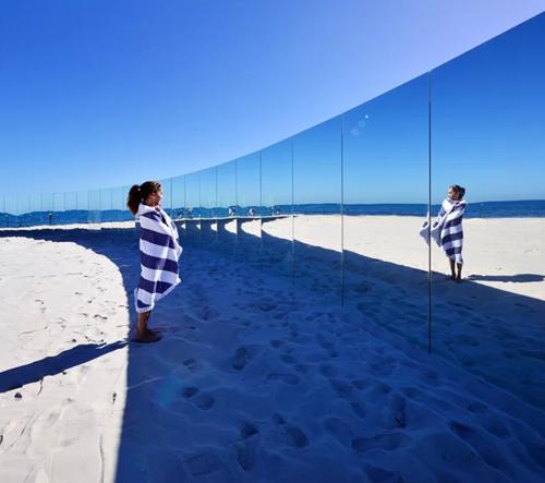 Zakřivená stěna zrcadel vyčnívá z písku na pláži v Austrálii