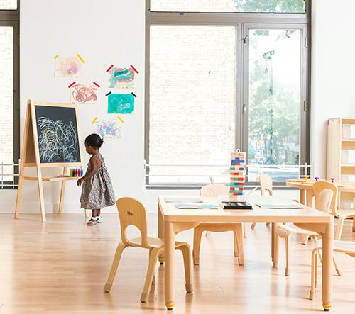 Interiér školy v Brooklynu je plný dřeva a pastelových barev